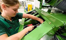 Auszubildende installiert die Batterieeinheit in eine Erntemaschine