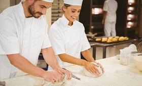 Ausbilder mit Auszubildender in Bäckerei beim Teig kneten