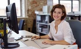 Auszubildende zur Kauffrau für Büromanagment an ihrem Arbeitsplatz