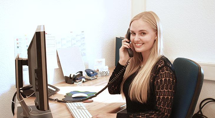 Kauffrau für Büromangement an ihrem Arbeitsplatz