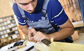 Tischlerazubi bearbeitet Holzbalken