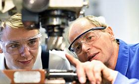 Auszubildender und Ausbilder an einer CNC Maschine