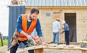 Handwerker mit Handkreissäge beim Hausbau