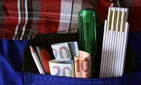 Handwerker mit Werkzeug und Geldscheinen in der Hosentasche
