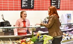 Auszubildende zur Kauffrau im Einzelhandel an Theke in Supermarkt