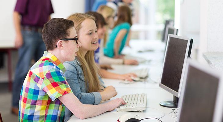 Schüler sitzen mit Freude am PC
