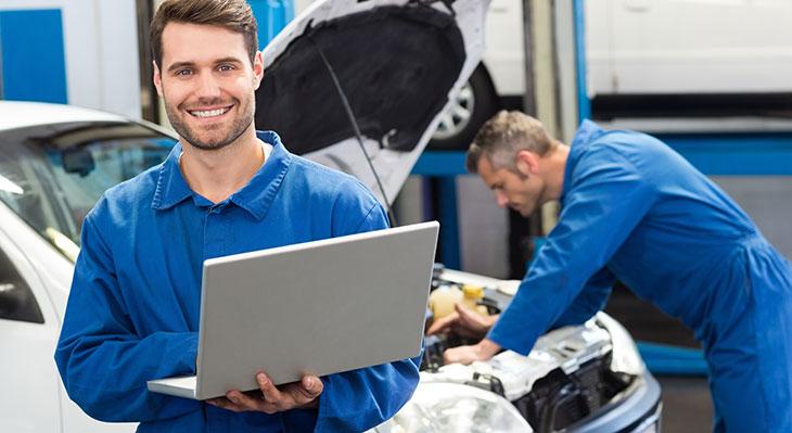 Kfz-Mechaniker-Azubi mit Laptop in Werkstatt