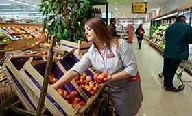 Verkäuferin sortiert Obstkisten
