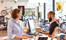 Kundin und Verkäufer in Fahrradwerkstatt